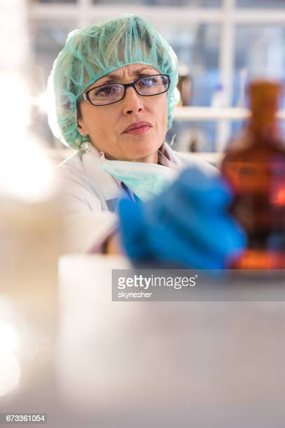 Mature female biotechnologist choosing the bottle for medical test in a laboratory.