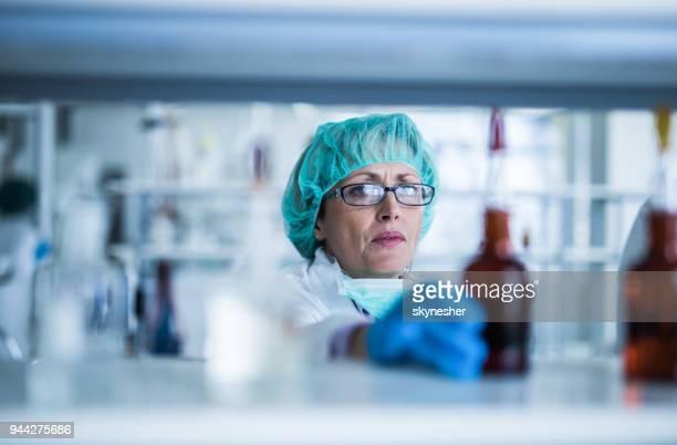 Mature female biotechnologist choosing the bottle for test.