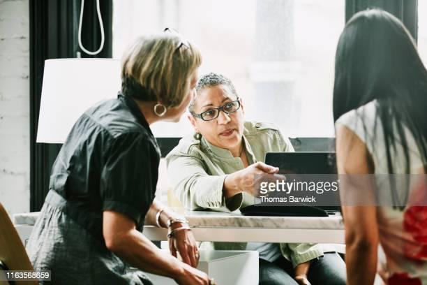 mature female business partners discussing project at desk in creative office - finanzwirtschaft und industrie stock-fotos und bilder