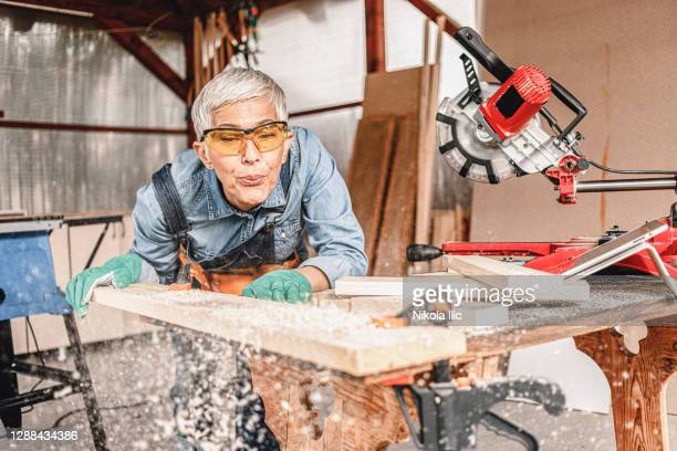 mature female carpenter cuts a piece of board with a miter saw. - mitre stock pictures, royalty-free photos & images