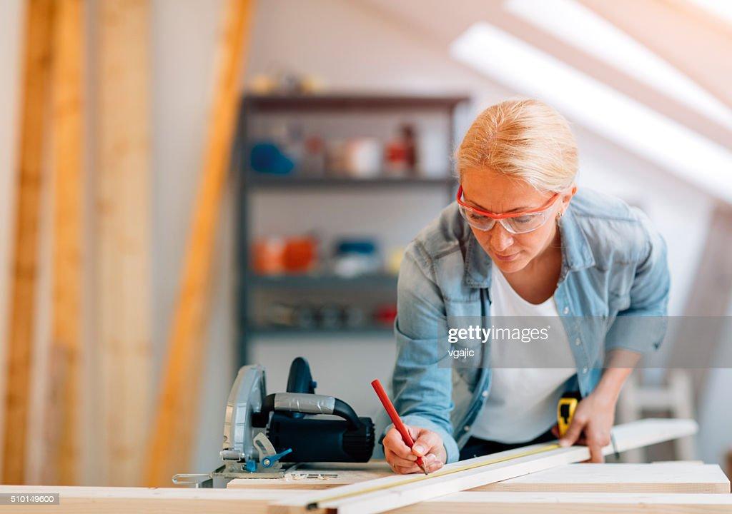 Mature female carpenter working in her workshop : Stock Photo