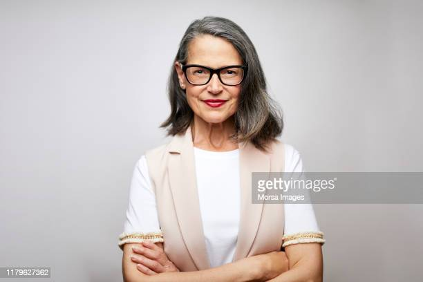 mature female ceo with arms crossed - white background stockfoto's en -beelden