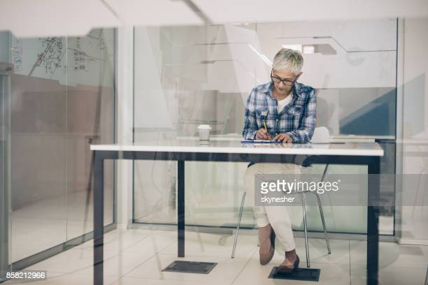 Mature female CEO writing at desk in her office.