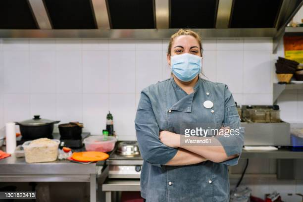 mature female chef with arms crossed in commercial kitchen during covid-19 - essential services stock pictures, royalty-free photos & images