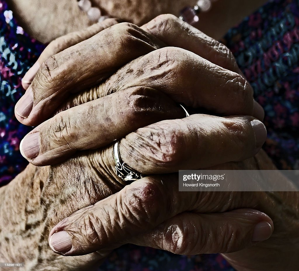 Mature female clasped hands : Stock Photo