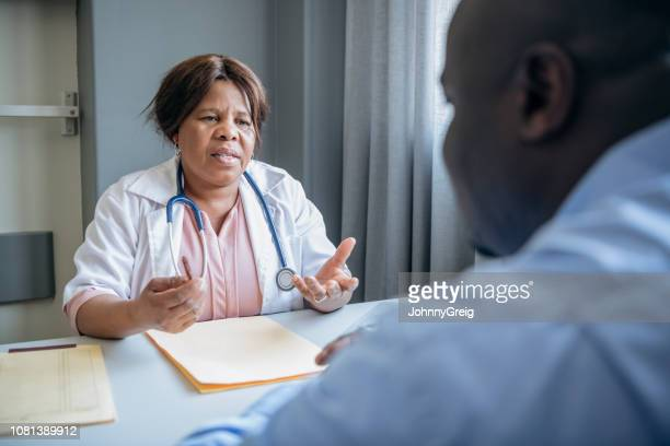 Mature female consultant explaining to patient in hospital