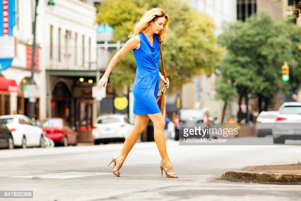 mature female crosses street in a hurry wearing heels - one mature woman only stock pictures, royalty-free photos & images