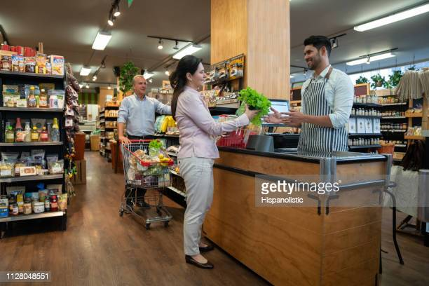 mature female customer handing a lettuce to friendly male cashier so he can scan product with bar code reader both smiling - cash register stock pictures, royalty-free photos & images