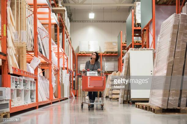 Mature female customer looking up while pushing shopping cart in hardware store