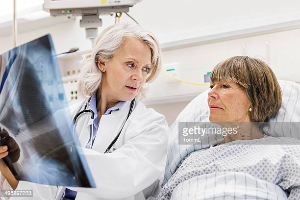 mature female doctor checking x-ray with mature patient - lung stock pictures, royalty-free photos & images