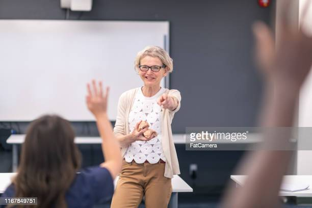 mature female doctor demonstrates expertise in training course with medical students - fatcamera stock pictures, royalty-free photos & images