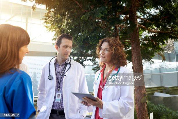 Mature female doctor holding digital tablet while discussing with colleagues outside hospital