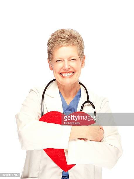 Mature female doctor hugging a heart smiling