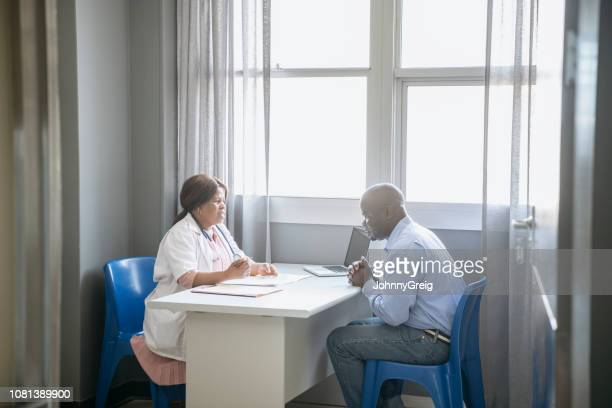 Mature female doctor in consultation with male patient