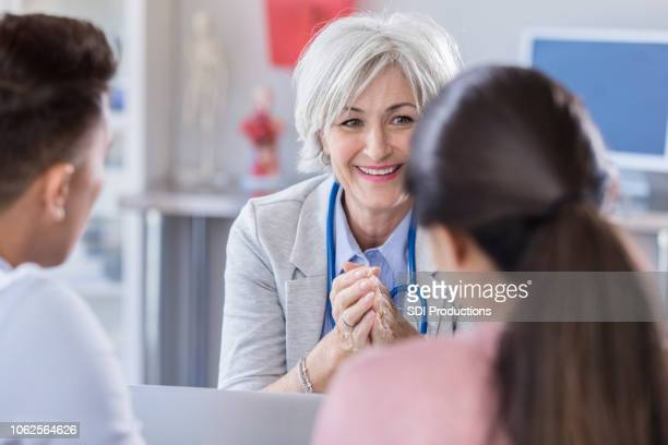 Mature female doctor shares exciting news with couple