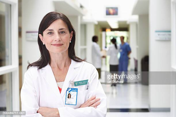 Mature female doctor standing in hallway, arms crossed