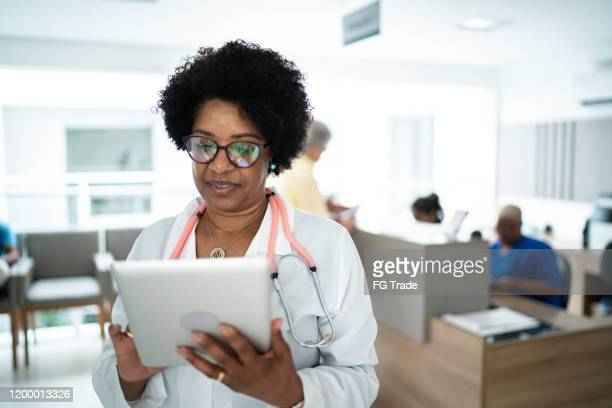 mature female doctor using digital tablet at medical office - telemedicine stock pictures, royalty-free photos & images