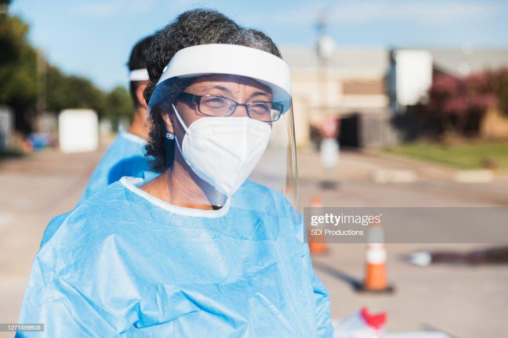 車両がCOVID-19検査場に近づくにつれて成熟した女性医師が見守る : ストックフォト