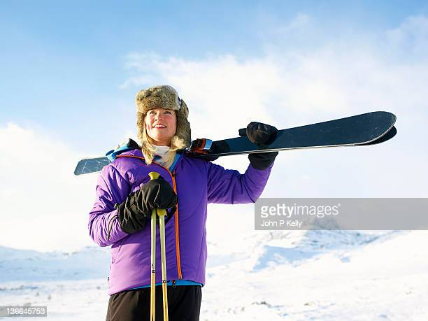 mature female downhill skier carrying skis - ski wear stock pictures, royalty-free photos & images