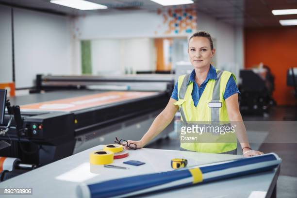 Mature female employee in Australia working in printing shop