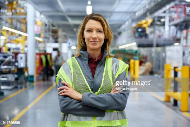 mature female engineer standing with arms crossed - reflective clothing stock pictures, royalty-free photos & images