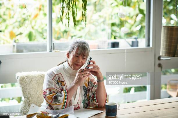 mature female entrepreneur holding mobile phone and listening to message - working seniors stock pictures, royalty-free photos & images
