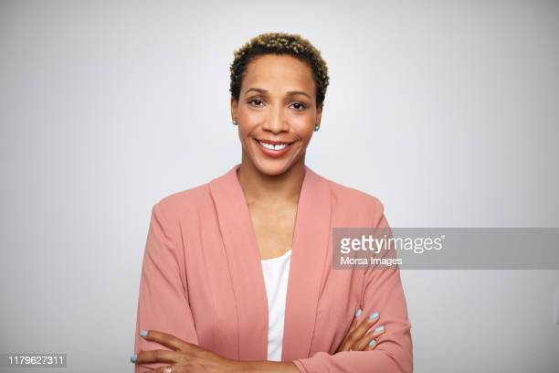 mature female entrepreneur with arms crossed - black blazer stock pictures, royalty-free photos & images