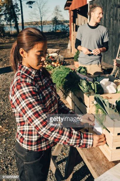 Mature female farmer sticking label on crate full of vegetables at market