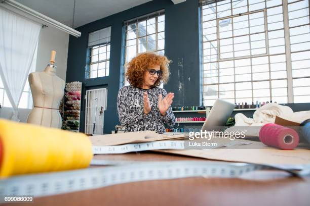Mature female fashion clapping at laptop on workshop table
