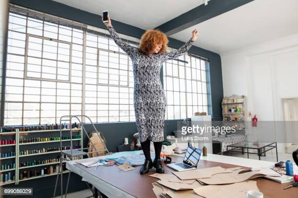 mature female fashion designer dancing to smartphone music on workshop table - older redhead stock pictures, royalty-free photos & images