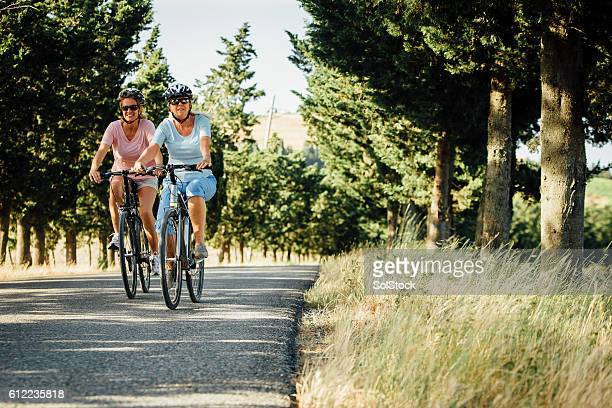 Mature Female Friends Cycling in Tuscany