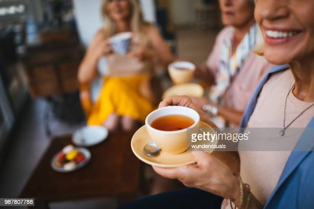 mature female friends enjoying a cup of tea at cafe - morning stock pictures, royalty-free photos & images