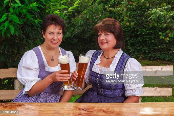 Mature Female Friends Holding Beer Glasses While Sitting At Park