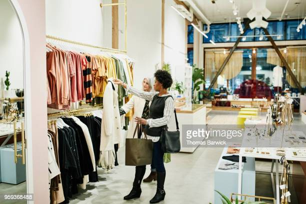 mature female friends looking at coat while shopping together in clothing boutique - black coat stock pictures, royalty-free photos & images