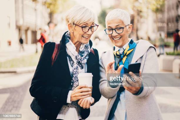 two mature female friends using smartphone