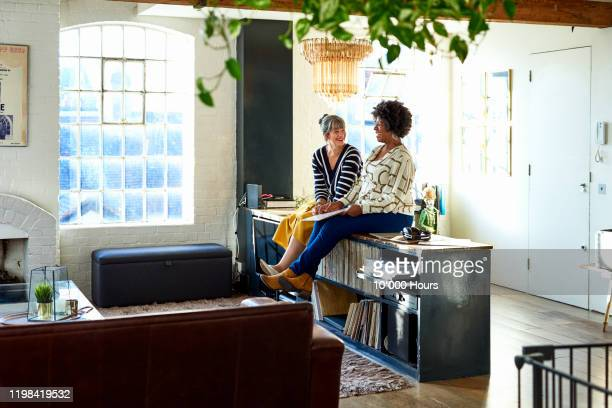 mature female friends talking at relaxing in loft apartment - female friendship stock pictures, royalty-free photos & images