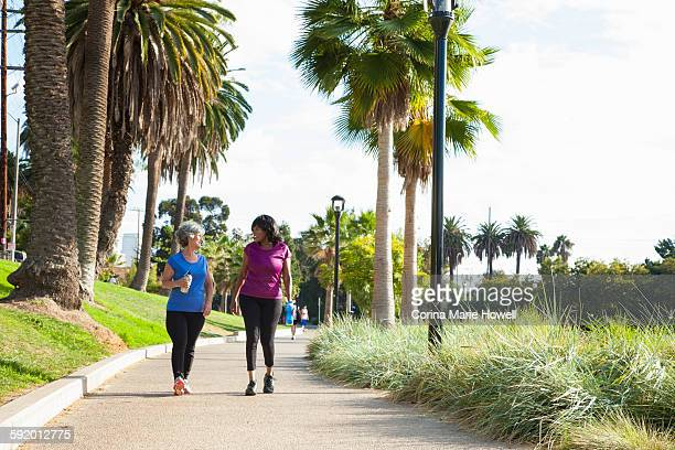 Mature female friends walking in park, holding water bottles