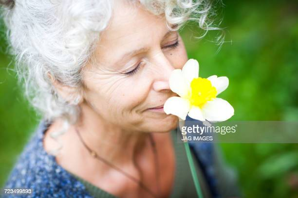 Mature female gardener smelling yellow daffodil