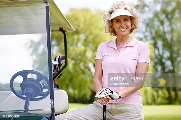 mature female golfer standing with her golf cart - women's golf stock pictures, royalty-free photos & images