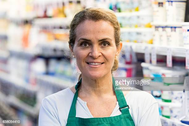 mature female grocery store worker - convenience store stock photos and pictures