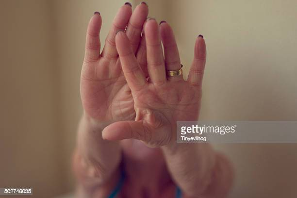 Mature female hands obscuring face