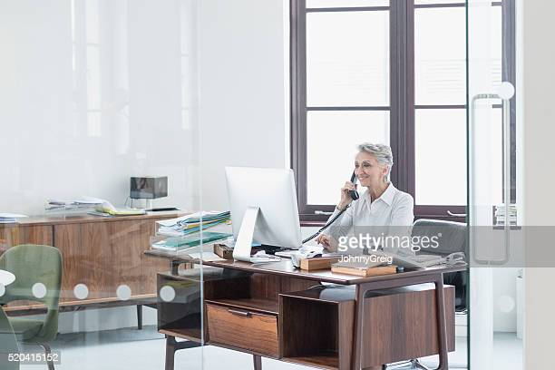 Reife weibliche Manager am Telefon im Büro