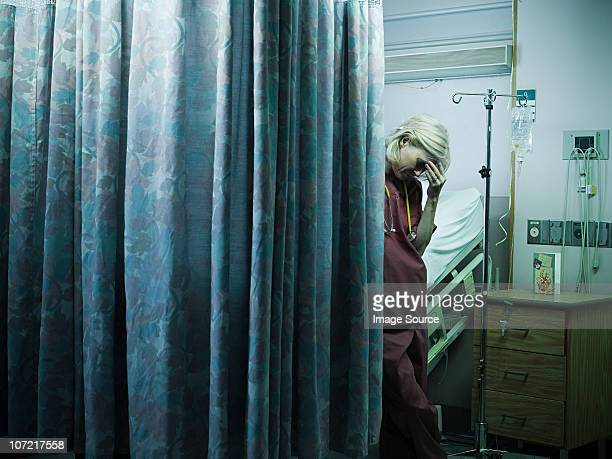mature female nurse with head in hands - death stock pictures, royalty-free photos & images