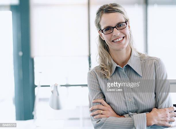 Mature female office worker smiling, arms folded, portrait