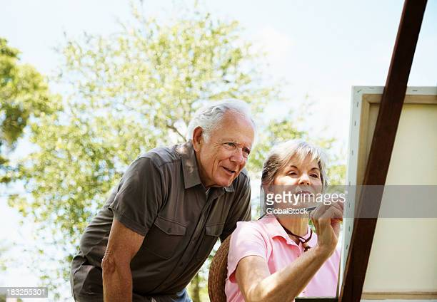 Mature female painting on canvas with her husband