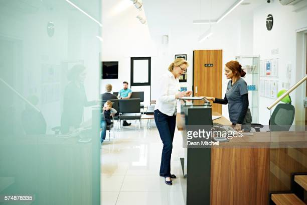 mature female patient at dental clinic - medical receptionist uniforms - fotografias e filmes do acervo