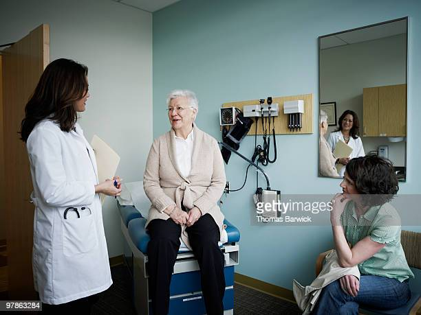 mature female patient in exam room with doctor - good news stock pictures, royalty-free photos & images