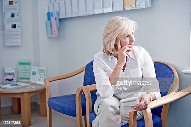 mature female patient in hospital waiting room - bulletin board flyer stock pictures, royalty-free photos & images