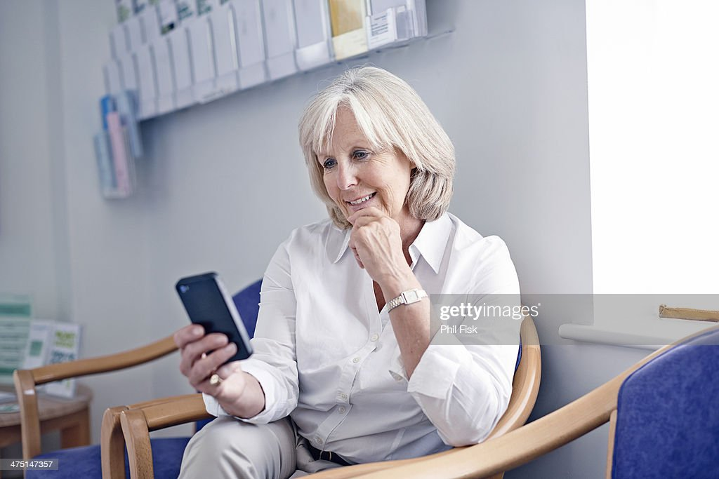 Mature female patient looking at mobile phone in hospital waiting room : Stock Photo