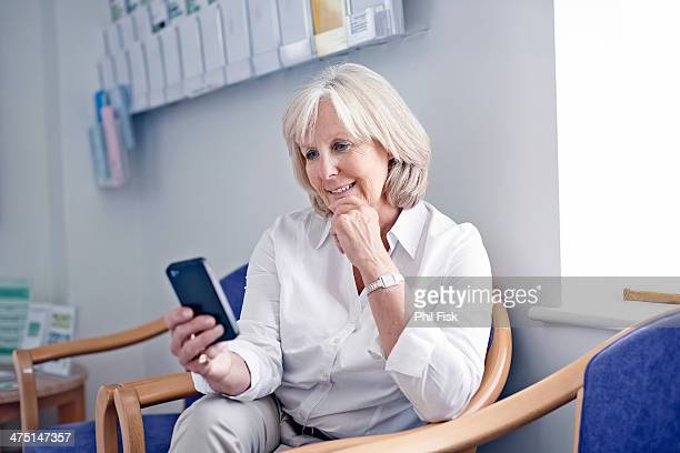 Mature female patient looking at mobile phone in hospital waiting room